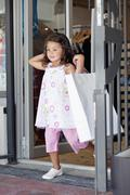 Cute little girl walking out of a shopping mall with shopping bags Stock Photos