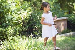 Side profile of a little girl walking in the garden - stock photo
