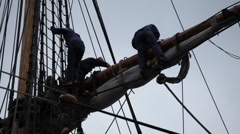 Tall ship sailors climbing in the rigging towards the sails Stock Footage