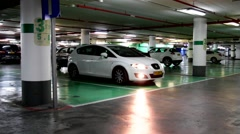 Underground garage with the moving  white car  with headlights Stock Footage