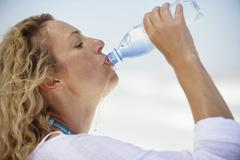 Side profile of a beautiful woman drinking purified water Stock Photos