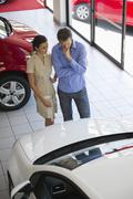 Female salesperson showing car to mid adult man in showroom Stock Photos