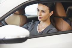 Beautiful young woman taking a test drive Stock Photos