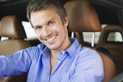 Portrait of a happy mid adult man taking a test drive Stock Photos