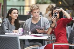 Three young friends sitting in a restaurant with one woman using camera - stock photo