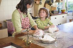 Grandmother and little boy kneading dough at kitchen - stock photo