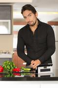 handsome young modern man cooking healthy recipe and using tablet - stock photo