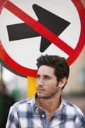 Handsome man thinking with no entry sign in the background Stock Photos