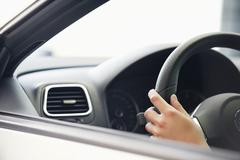 Close-up of a human hand on car steering wheel - stock photo