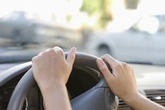 Close-up of human hand holding steering wheel - stock photo
