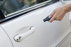 Person's hand unlocking the car with remote control Stock Photos