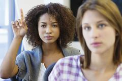 Two women sitting in classroom with focus on African American woman raising hand - stock photo