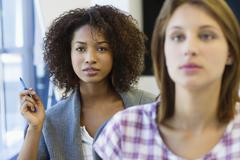 Two women sitting in classroom with focus on African American woman - stock photo