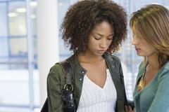 Caucasian woman consoling to an African American woman in university - stock photo