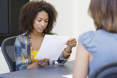 African American woman reading a resume while taking interview of a Caucasian - stock photo