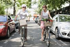 Couple carrying vegetables on bicycles, Paris, Ile-de-France, France - stock photo