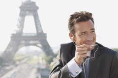 Businessman using a hands-free device with the Eiffel Tower in the background, Stock Photos