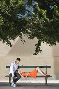Couple on a bench in a garden, Terrasse De l'Orangerie, Jardin des Tuileries, - stock photo