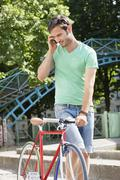 Man walking with a bicycle and talking on a mobile phone, Paris, Ile-de-France, - stock photo