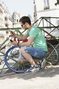 Man locking his bicycle, Paris, Ile-de-France, France Stock Photos