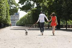 Couple running in a garden with a puppy, Terrasse De l'Orangerie, Jardin des - stock photo