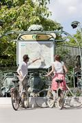 Couple with bicycles looking at a map, Paris, Ile-de-France, France - stock photo