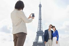 Woman taking a picture of couple with the Eiffel Tower in the background, Paris, Stock Photos