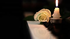 White Rose and Candle on Piano Keys Stock Footage
