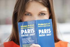 Portrait of a woman holding a travel guidebook in front of her face, Paris, Stock Photos
