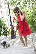 Woman holding a puppy on leash and talking on a mobile phone, Montmartre, Paris, Stock Photos