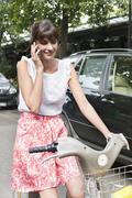 Woman riding a bicycle and talking on a mobile phone, Paris, Ile-de-France, - stock photo