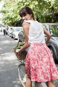Woman carrying vegetables on a bicycle, Paris, Ile-de-France, France - stock photo