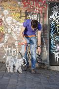Man showing feces to his puppy, Paris, Ile-de-France, France Stock Photos