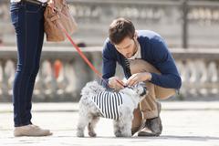 Man attaching leash on a puppy, Paris, Ile-de-France, France Stock Photos