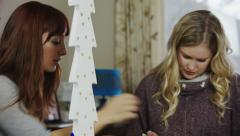 Two women helping each other with ideas in a craft room Stock Footage
