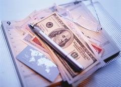 International Currency, Pen Agenda and Eyeglasses - stock photo