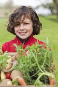 Happy boy with a crate of homegrown vegetables Stock Photos