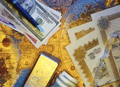 International Currency, Pen Stock Certificates and Gold Bar On Antique World Map - stock photo