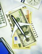 International Currency and Toy Airplane on Notebook with Cell Phone and - stock photo