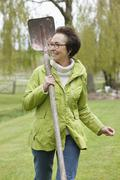 Woman walking with a spade in a park Stock Photos