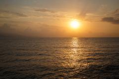 The sun rising over the sea Stock Photos
