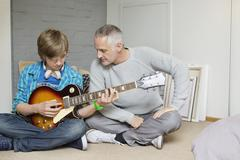 Teenage boy learning guitar with his father at home - stock photo