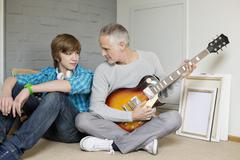Man playing a guitar with his son at home Stock Photos