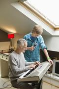 Man playing an electric piano with his son at home Stock Photos