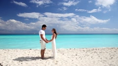 Young beautiful newlyweds doing  pledge of allegiance on beach Stock Footage