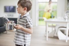 Boy carrying a saucepan Stock Photos