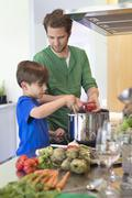 Boy assisting his father in the kitchen - stock photo