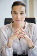 Portrait of a businesswoman with her hands clasped in an office - stock photo