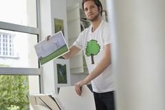 Man holding an ecological poster showing wind turbine - stock photo
