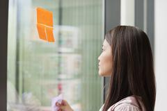 Businesswoman sticking memo notes on glass in an office Stock Photos